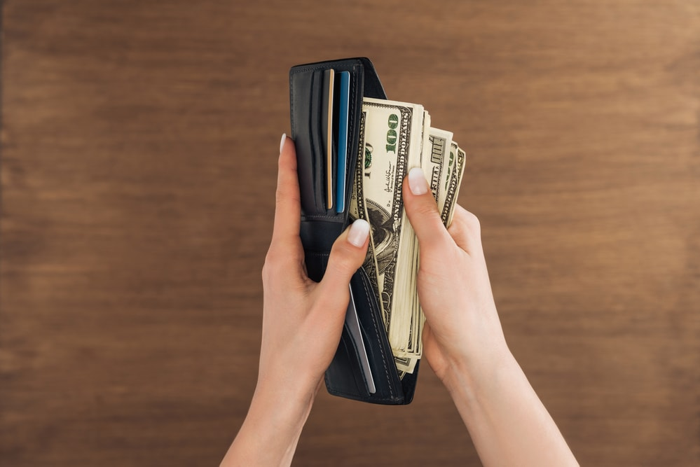 putting money into wallet